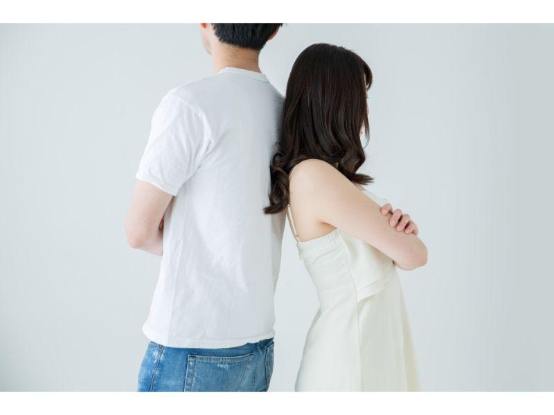 喧嘩して背中を合わせるカップルの写真