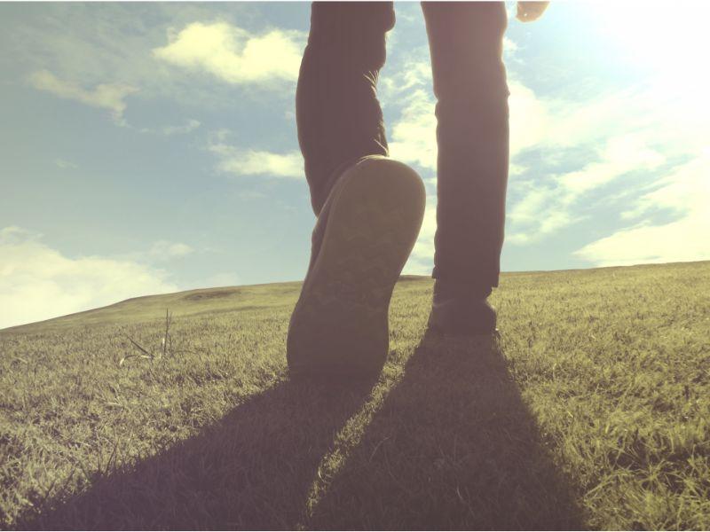 1歩を踏み出す男性の足元の写真