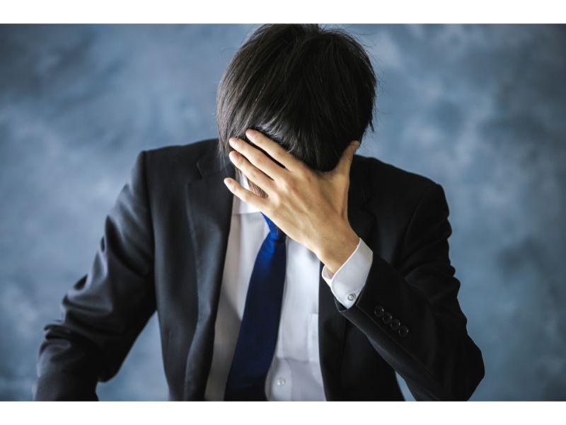 顔を手で覆い泣く男性の写真