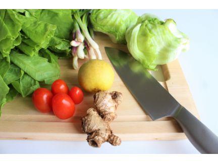 まな板の上に多くの野菜と包丁が置いている画像