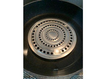 大きなフライパンの底に蒸し目皿を入れ水を張った画像