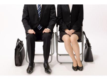 面接前に椅子に座っている男女の写真