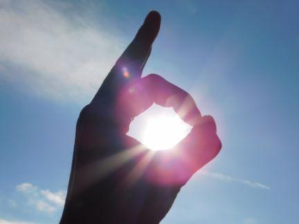 手でOKを作り、太陽にかざしている写真
