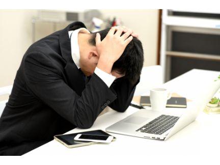 デスクの上で頭を抱える男性の写真
