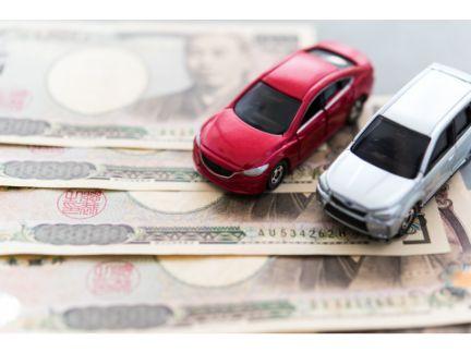 1万円札の上にミニカー2台、車を買うか選択する写真