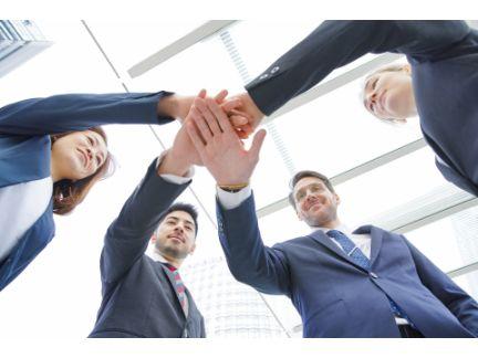 同僚4人が手を合わせ団結している写真
