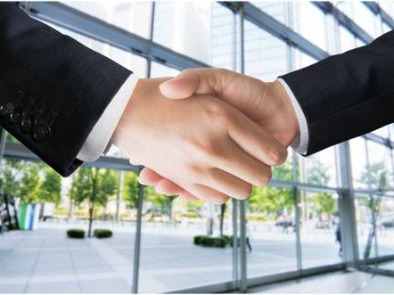男性同士が握手している手だけアップした写真