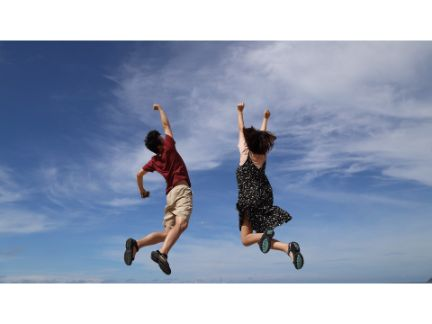 大空に向かって大きくジャンプする男女の写真