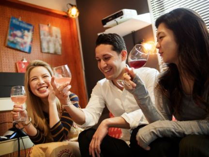 女子2人の間に挟まれ笑顔で話す男性の写真