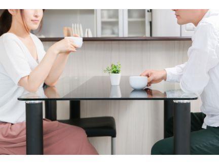 机で男女が向かい合いで座りコーヒーを飲んでいる写真