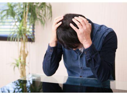 頭を抱えて悩み男性の写真