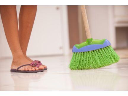 ほうきでゴミをはく女性の足元の写真