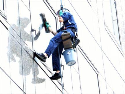 ブルの窓を拭く清掃員の写真