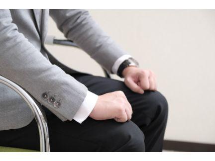 膝の上に手を置いて面接を受ける男性