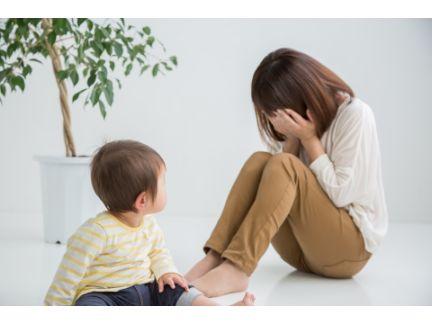子供の横で泣く母親の写真