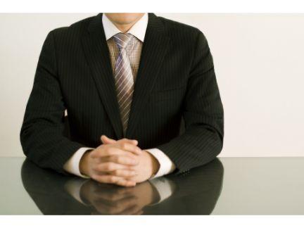 男性が座って報告をしている様子の写真