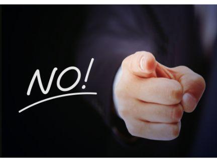 男性が「NO」を指さす写真