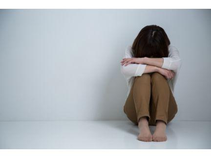 膝を抱え悩んでいる女性の写真