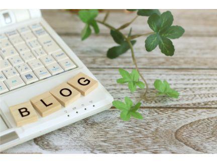 パソコンの隅に木製の「BLOG」文字を並べている写真
