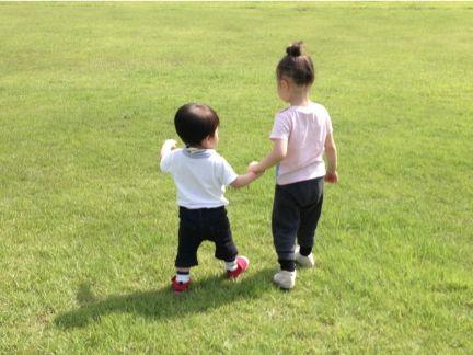 男の子と女の子が手を繋いでいる後ろ姿の写真