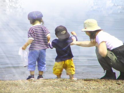 浜辺で遊ぶ子供2人と母親の写真