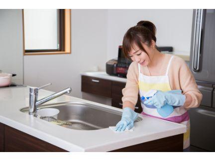 シンクを掃除する女性の写真