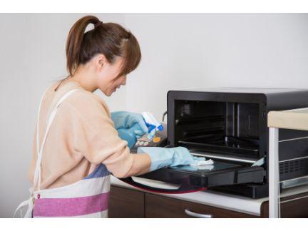 電子レンジを掃除している女性の写真