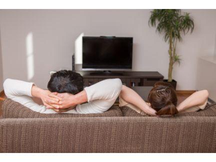 ソファーでくつろぐ男女の後ろ姿