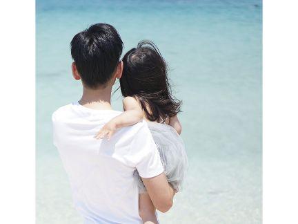 子供を抱っこして海を眺める男性の写真