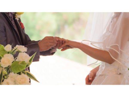 結婚式で新郎が新婦へ指輪をはめる写真