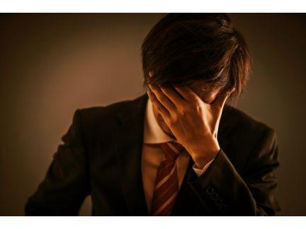 顔を片手で押さえ悩む男性の写真