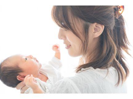 赤ちゃんを抱き微笑む母親の写真