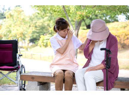 高齢女性が泣いているのを励ます介護士の女性の写真