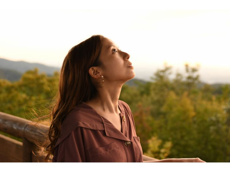 遠くを眺め黄昏ている女性の写真