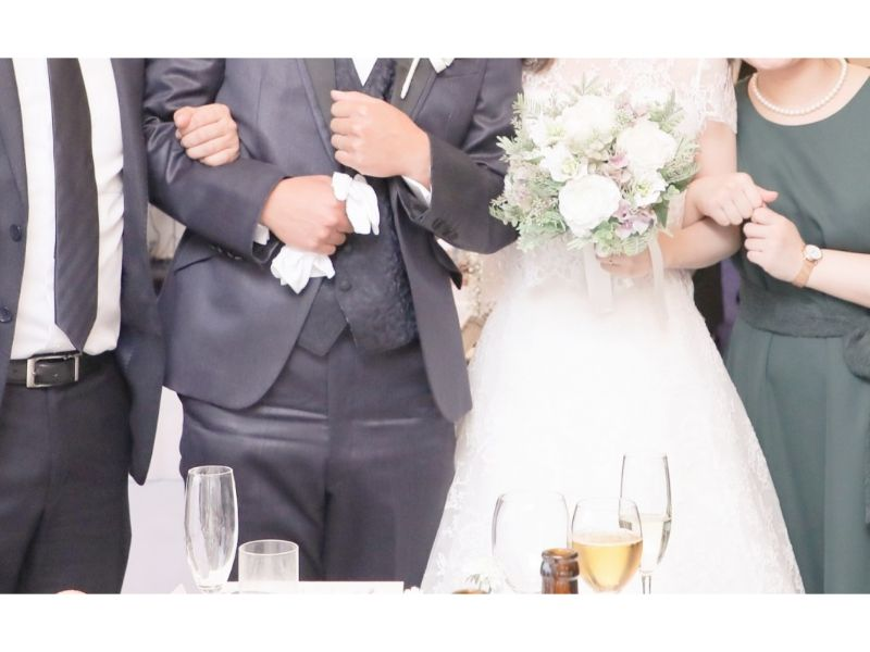 結婚式で新郎新婦と友人で腕を組んで撮影