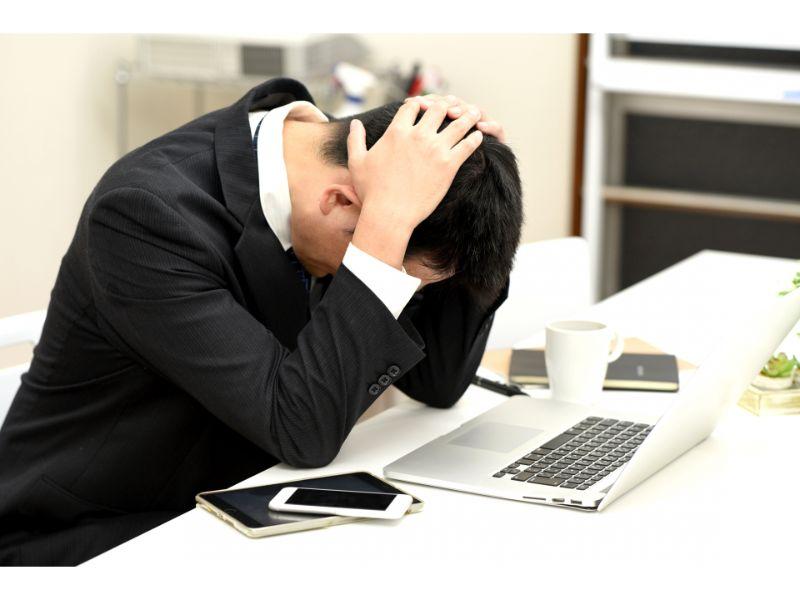 パソコンを開いて頭を抱え悩む男性の写真