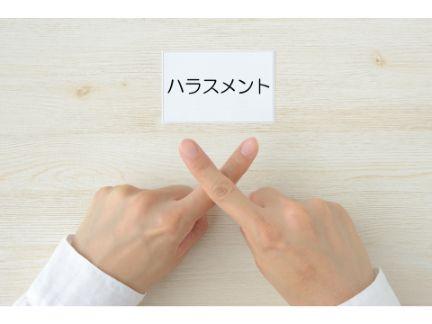 ハラスメントと書かれた紙と女性が指でバツ印をする写真