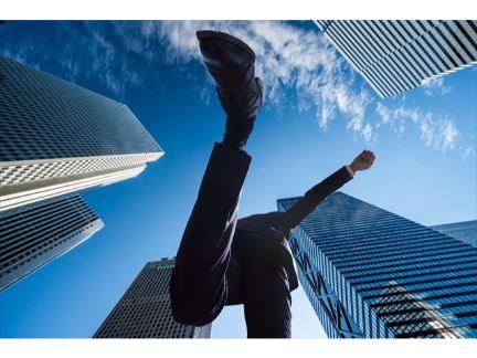 都会の中を飛び超える男性の写真