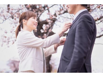 男性のネクタイを直す女性の写真