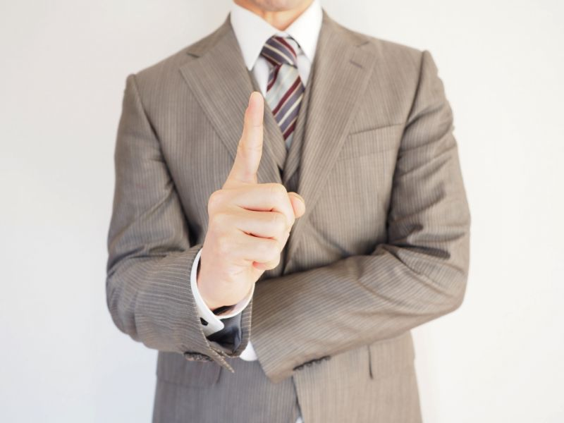 人差し指を立てる男性の写真