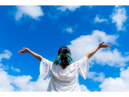 大空に両手を広げて立つ女性の後ろ姿の写真