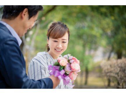 男性が女性に花束を渡している写真