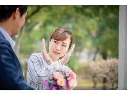 告白する男性と、両手でバツをして断る女性の写真