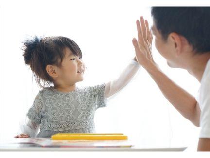 子供とハイタッチする父親の写真