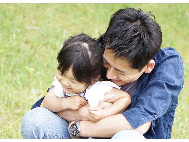 後ろから子供を抱きしめる父親の写真