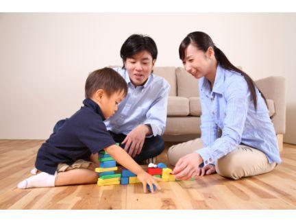 ブロック遊びをする子供を微笑んで見守る夫婦の写真
