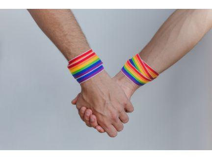 LGBTを表すレインボーのリストバンドをしたカップルが手を繋いでいる写真