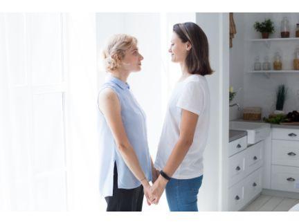 女性同士のカップルが向き合って手を繋いでいる写真
