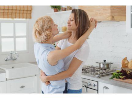 キッチンで抱き合う女性カップルの写真