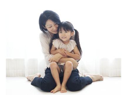 子供を膝の上で抱っこする母親の写真